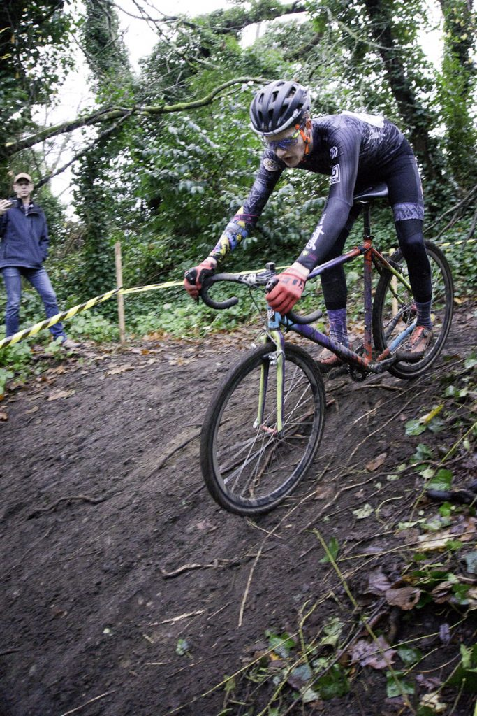 Cyclocross racer descends steep wooded and rooted section