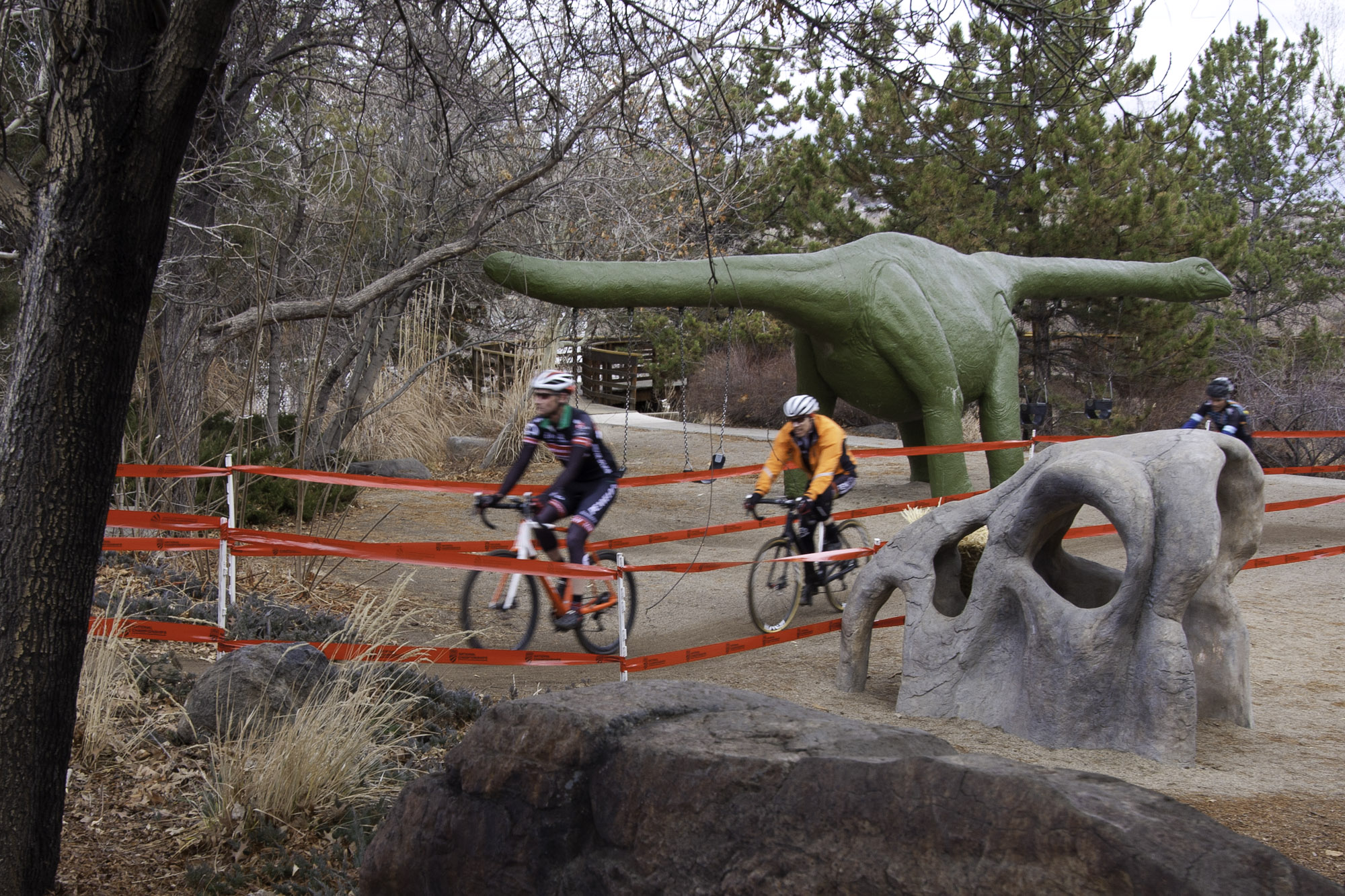 Cyclocross racers ride through a dinasaur themed playground