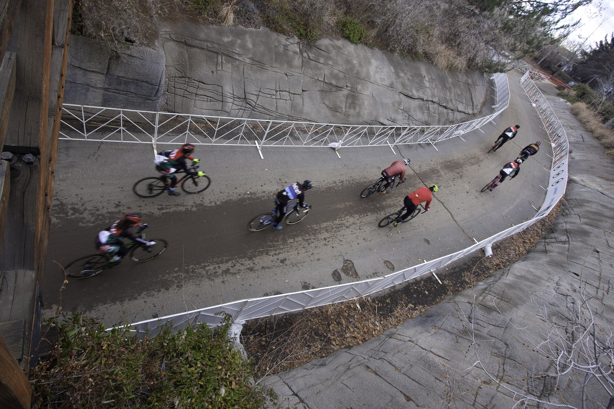 Cyclists ride under a bridge during a Cyclocross race