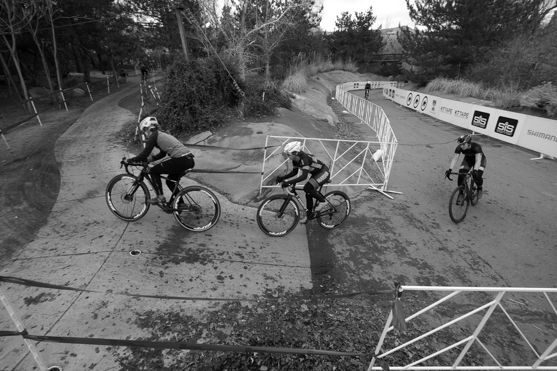 Three cyclocross racers cornering on pavement