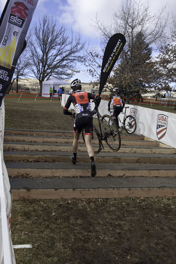 Cyclocross racer running bike up plywood steps