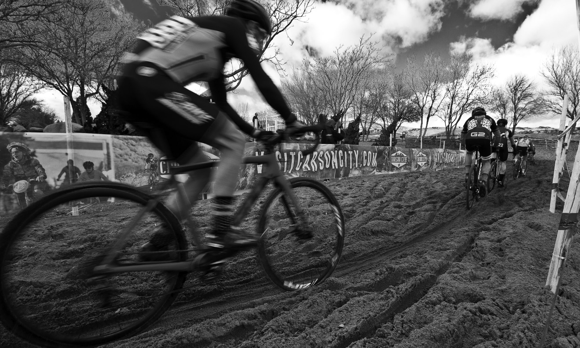 Cyclocross racers riding the sand feature